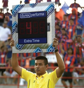 A soccer official holds the extra time sign shaped like a condom wrapper